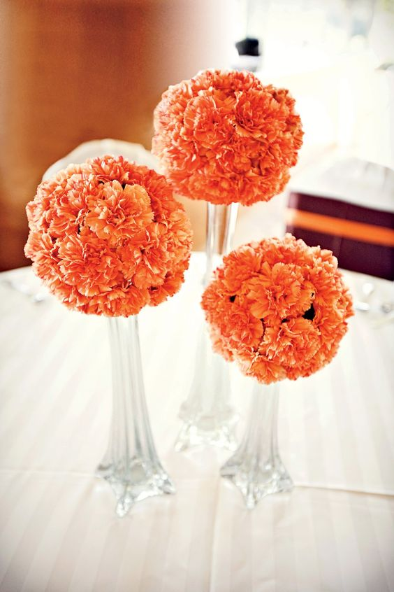 orange carnations at wedding table arrangements